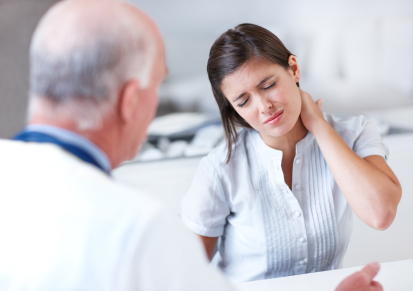 Young woman wincing with pain in a consultation with her doctor - copyspace